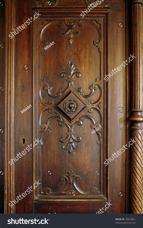 A Picture Of A Wooden Carved Door Of An Antique Closet